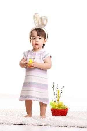 Baby girl in easter bunny costume, standing beside easter basket and holding toy chicken, looking amazed. Isolated on white background. photo