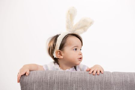 Closeup portrait of baby girl in easter bunny costume, smiling. Isolated on white background. photo
