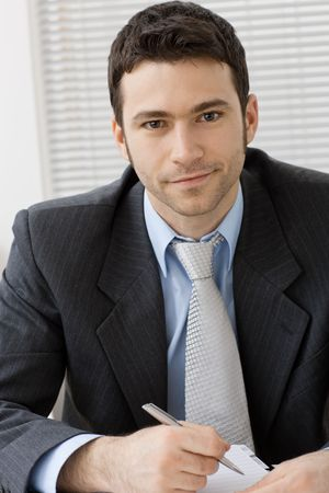 Portrait of young and happy businessman at office desk, smiling. Stock Photo - 6285772