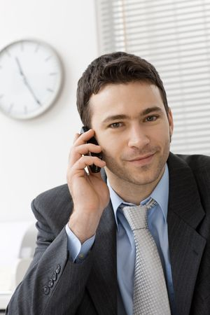 Happy businessman talking on mobile phone in office, smiling. photo