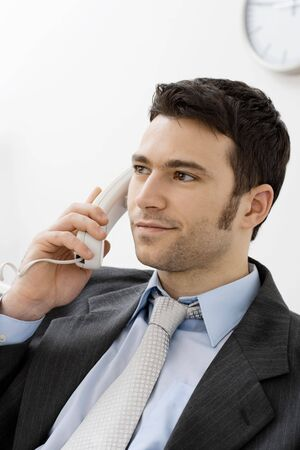Closeup of businessman sitting at desk in office, talking on landline phone, smiling. photo
