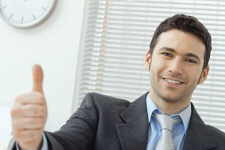 Businessman showing OK sign with his thumb up. Selective focus on face. photo