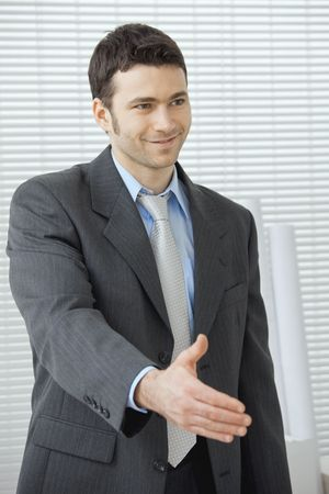 Young businessman in grey suit and blue shirt, standing with open hand, ready to set a deal. Stock Photo - 6285815
