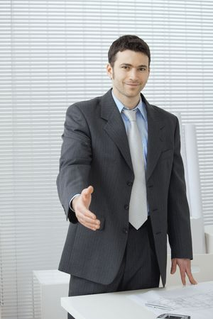 Young businessman in grey suit and blue shirt, standing with open hand, ready to set a deal. Stock Photo - 6285812