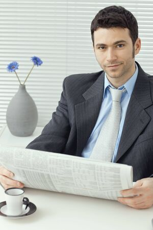 Young businessman having a morning coffee break, sitting at desk and reading business news. Stock Photo - 6285761