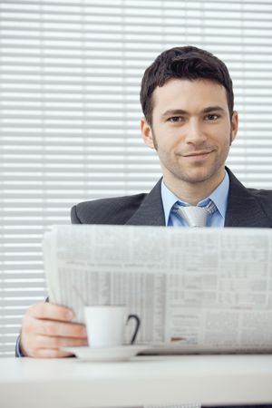 Young businessman having a morning coffee break, sitting at desk and reading newspaper. Stock Photo - 6285783