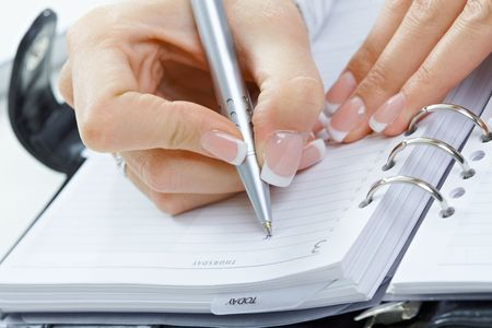 Closeup of female hand writing notes into personal organizer. Stock Photo - 6285781