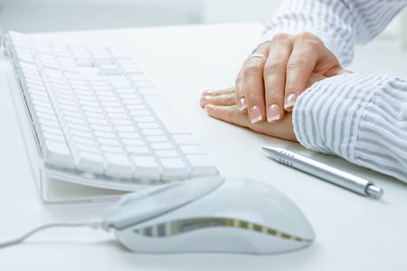 Closeup picture of female hands on desk, beside computer keyboard, mouse and pen. photo