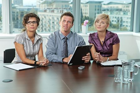 applicant: Panel of business people sitting at table in meeting room conducting job interview. Stock Photo