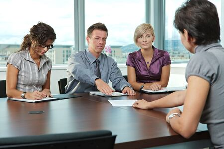 applicant: Panel of business people sitting at table in meeting room conducting job interview. Applicant showing documents.  Stock Photo