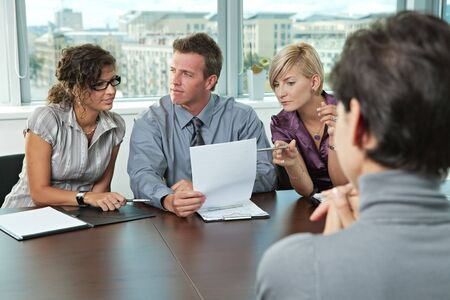 conducting: Panel of business people sitting at table in meeting room conducting job interview looking at documents.