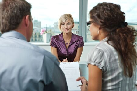 Attractive woman applicant talking during job interview. Over the shoulder view. photo