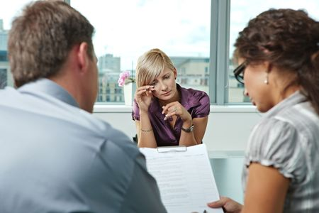 Woman applicant crying during job interview. Over the shoulder view.
