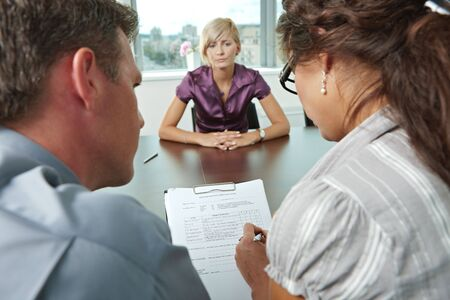 job promotion: Woman applicant worrying during job interview. Over the shoulder view. Focus placed on sheet in front all results are bad.