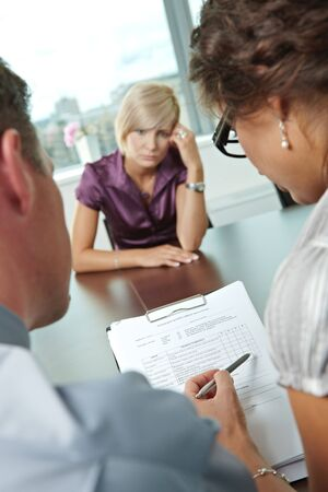 Woman applicant having failed job interview. Over the shoulder view. Focus placed on sheet in front all results are bad. photo