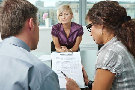 entrevista de trabajo: Mujer solicitante preocupante durante la entrevista de trabajo. En la vista de hombro. Enfoque que se coloca en la hoja en el frontales de los resultados son buenos. Foto de archivo