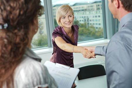 attire: Business people shaking hands over meeting table at office, smiling.