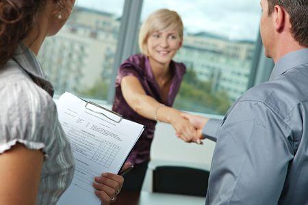 entrevista de trabajo: Entrevista de trabajo exitosa - feliz empleado agitando las manos, sonrientes. Lugares se centran en questionnarie en el frente, reults son excelentes.  Foto de archivo