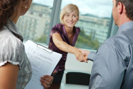 Successful job interview - happy employee shaking hands, smiling. Focus places on questionnarie in front, reults are excellent.  photo