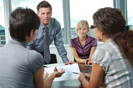 четыре человека: Группа молодых деловых людей говорить на деловой встрече в офисе.