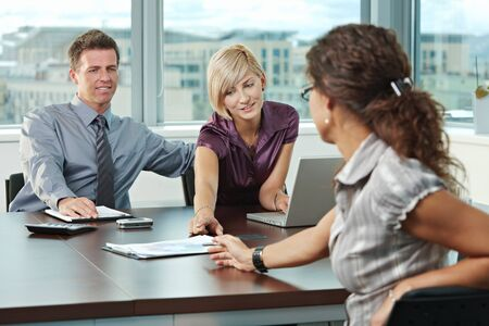 fulfilled: Young business people planning on table at office during business meeting.