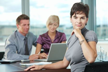 Smiling businesswoman on business meeting at office with team in background. Stock Photo - 6285985