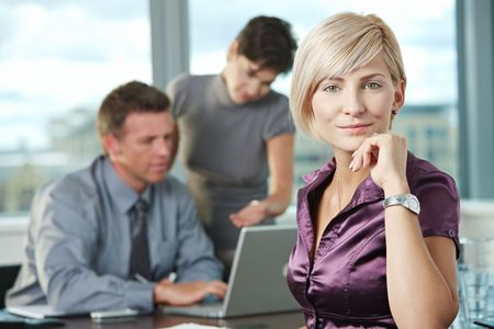 appealing attractive: Smiling businesswoman on business meeting at office with team in background.