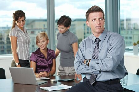 Confident businessman at office with business team in background. photo