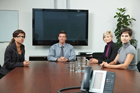 Business people sitting around meeting table in board room, waiting, looking at camera. Blank space on screen for your logo or text. photo