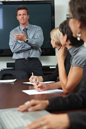 explaining: Businessman conducting business training, people sitting in a row, listening.
