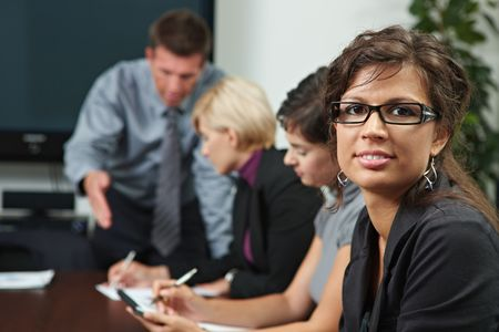 Businesswoman looking at camera during business training, smiling. photo
