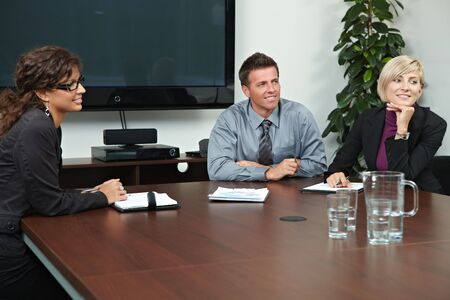 Business people sitting around meeting table in board room, talking. Stock Photo - 6285994