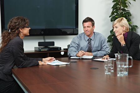 Business people sitting around meeting table in board room, talking. photo