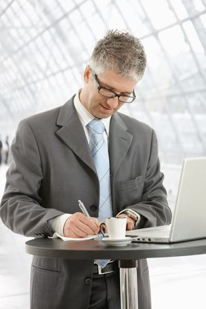 Businessman writing notes on paper standing at coffee table in office lobby. photo