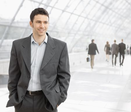 office wear: Young businessman standing in office hallway with hands in his pocket, smiling.