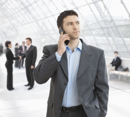 Young businessman talking on mobile standing in office hallway. Stock Photo - 6286138