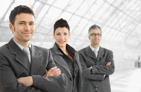 together with long tie: Permanente del equipo de negocio en el vest�bulo de la Oficina, mirando a c�mara, sonriendo.