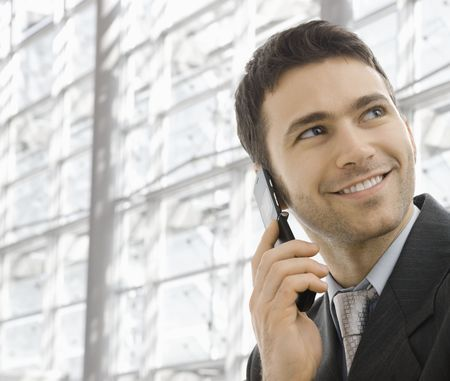 Closeup portrait of happy businessman talking on mobile in front of office building windows. Stock Photo - 6286132