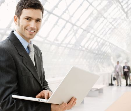 iş adamı: Happy young businessman using laptop in business building, smiling.
