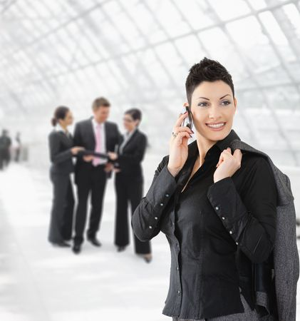 Portrait of happy businesswoman talking on mobile phone on office hallway. Stock Photo - 6286021