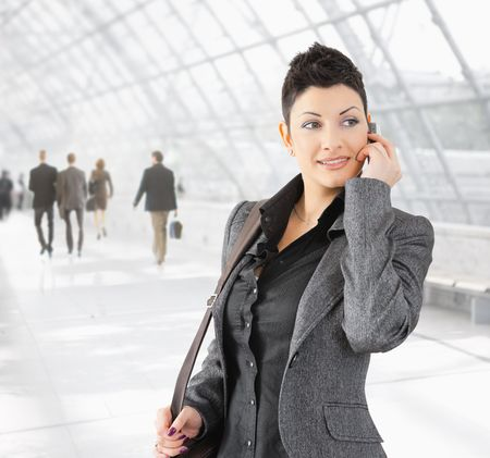 Portrait of young businesswoman talking on mobile phone on office hallway. Stock Photo - 6286105