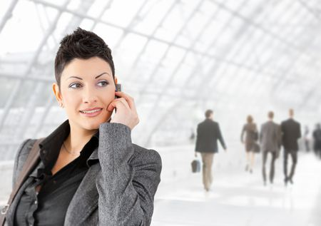 Young businesswoman talking on mobile phone on office lounge, smiling. photo