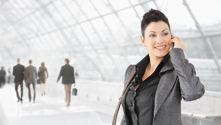 Happy businesswoman talking on mobile phone on office hallway, smiling. photo