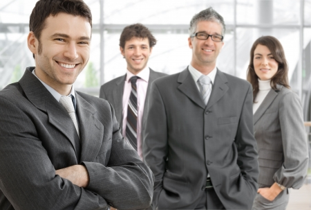 gratified: Group of four happy business people wearing gray suit, businessman leading team, smiling. Stock Photo