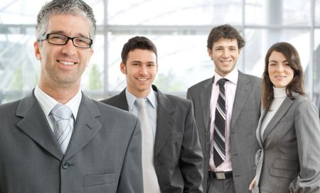 Group of four happy business people wearing gray suit, businessman leading team, smiling. Stock Photo - 6286130