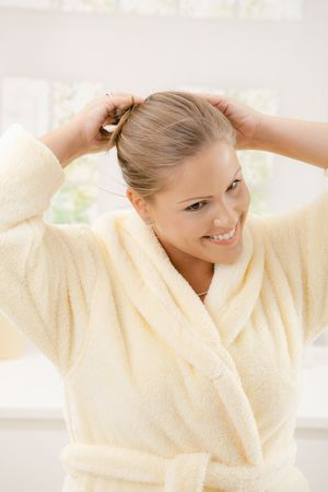 house robes: Portrait of happy young woman wearing yellow bathrobe, smiling. Stock Photo