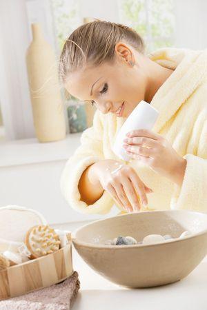 house robes: Happy young woman wearing bathrobe, using hand cream, smiling.