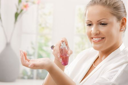 Young woman wearing white silk bathrobe applying perfume, smiling.