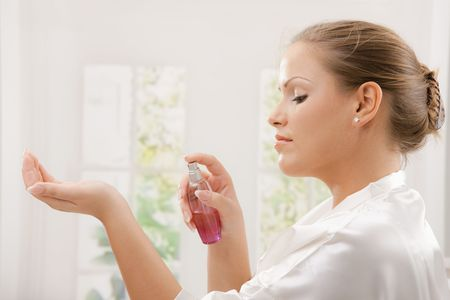 scents: Profile portrait of young woman wearing white silk bathrobe applying perfume.