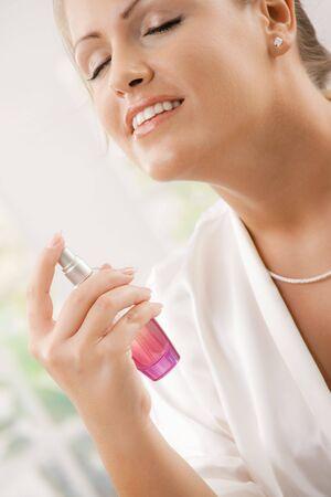 expresion corporal: Detalle de joven vistiendo Albornoz de seda blanca aplicar perfume, foco por lado.